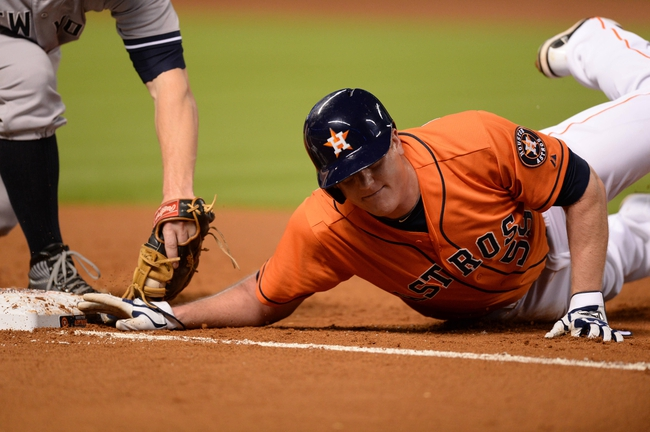 Sep 27, 2013; Houston, TX, USA; Houston Astros left fielder Marc Krauss (59) beats the throw back to New York Yankees first baseman Mark Reynolds (39) during the second inning at Minute Maid Park. Mandatory Credit: Thomas Campbell-USA TODAY Sports
