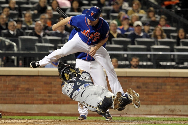 Sep 27, 2013; New York, NY, USA; New York Mets second baseman Daniel Murphy (28) leaps over Milwaukee Brewers catcher Martin Maldonado (12) while attempting to score during the sixth inning of a game at Citi Field. Maldonado missed the tag but Murphy missed the plate and was eventually tagged out. Mandatory Credit: Brad Penner-USA TODAY Sports