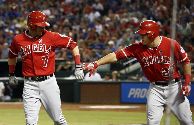 Sep 27, 2013; Arlington, TX, USA; Los Angeles Angels third baseman Andrew Romine (7) is congratulated by designated hitter Mike Trout (27) after scoring a run against the Texas Rangers during the third inning of a baseball game at Rangers Ballpark in Arlington. Mandatory Credit: Jim Cowsert-USA TODAY Sports