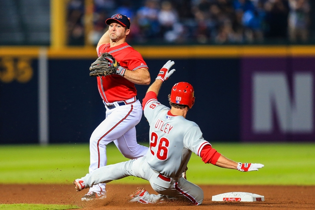 Sep 27, 2013; Atlanta, GA, USA; Atlanta Braves second baseman Dan Uggla (26) turns a double play over Philadelphia Phillies second baseman Chase Utley (26) in the seventh inning at Turner Field. Mandatory Credit: Daniel Shirey-USA TODAY Sports