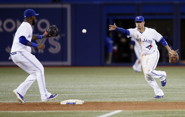 Sep 27, 2013; Toronto, Ontario, CAN; Toronto Blue Jays second baseman Ryan Goins (17) tosses the ball to shortstop Jose Reyes (7) to start a double play against the Tampa Bay Rays in the eighth inning at Rogers Centre. Toronto defeated Tampa Bay 6-3. Mandatory Credit: John E. Sokolowski-USA TODAY Sports