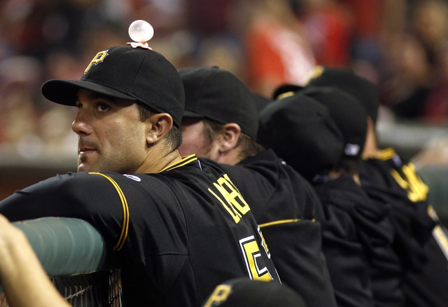 Sep 27, 2013; Cincinnati, OH, USA; Pittsburgh Pirates right fielder Andrew Lambo (left) watches from the dugout in the ninth inning during a game against the Cincinnati Reds at Great American Ball Park. Pittsburgh won 4-1. Mandatory Credit: David Kohl-USA TODAY Sports