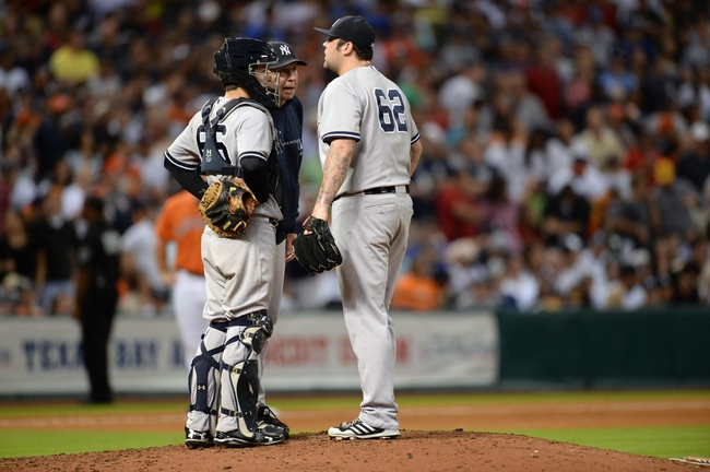 Sep 27, 2013; Houston, TX, USA; New York Yankees pitching coach Larry Rothschild (58) talks to relief pitcher Joba Chamberlain (62) against the Houston Astros during the seventh inning at Minute Maid Park. Mandatory Credit: Thomas Campbell-USA TODAY Sports