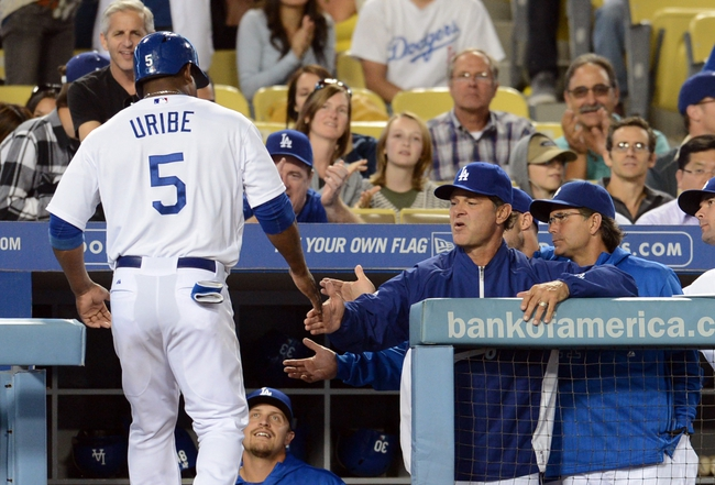 Sep 27, 2013; Los Angeles, CA, USA;  Los Angeles Dodgers third baseman Juan Uribe (5) heads to the dugout after scoring a run in the first inning against the Colorado Rockies at Dodger Stadium. Mandatory Credit: Jayne Kamin-Oncea-USA TODAY Sports