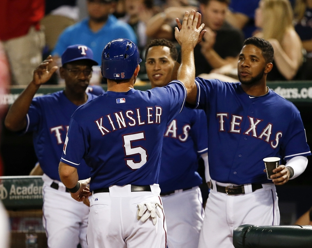 Sep 27, 2013; Arlington, TX, USA; Texas Rangers second baseman Ian Kinsler (5) is congratulated by manager Ron Washington (left), center fielder Leonys Martin (center) and shortstop Elvis Andrus (right) after scoring a run against the Los Angeles Angels during the seventh inning of a baseball game at Rangers Ballpark in Arlington. The Rangers won 5-3. Mandatory Credit: Jim Cowsert-USA TODAY Sports