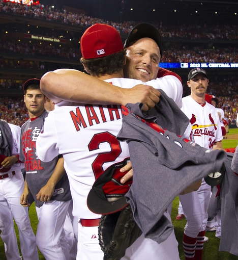 Sep 27, 2013; St. Louis, MO, USA; St. Louis Cardinals manager Mike Matheny (22) and Cardinals left fielder Matt Holliday (7) celebrate after the game against the Chicago Cubs at Busch Stadium. The Cardinals defeated the Cubs 7-0 to win the National League Central Title. Mandatory Credit: Scott Rovak-USA TODAY Sports