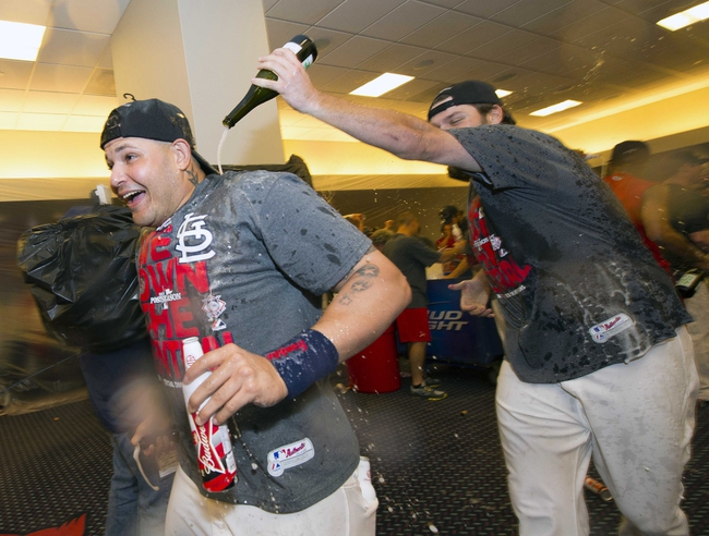 Sep 27, 2013; St. Louis, MO, USA; St. Louis Cardinals starting pitcher Lance Lynn (31) sprays Cardinals catcher Yadier Molina (4) with champagne after the game against the Chicago Cubs at Busch Stadium. The Cardinals defeated the Cubs 7-0 to win the National League Central Title. Mandatory Credit: Scott Rovak-USA TODAY Sports