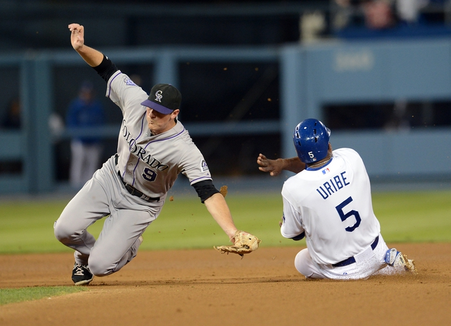 Sep 27, 2013; Los Angeles, CA, USA; Colorado Rockies second baseman DJ LeMahieu (9) reaches for the throw as Los Angeles Dodgers third baseman Juan Uribe (5) steals second base in the third inning of the game at Dodger Stadium. Mandatory Credit: Jayne Kamin-Oncea-USA TODAY Sports