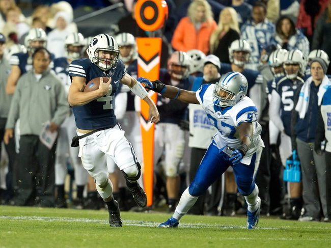 Sep 27, 2013; Provo, UT, USA; Brigham Young Cougars quarterback Taysom Hill (4) runs away from Middle Tennessee Blue Raiders defensive end Jiajuan Fennell (97) during the second half at Lavell Edwards Stadium. Brigham Young won 37-10. Mandatory Credit: Russ Isabella-USA TODAY Sports