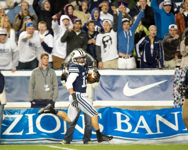 Sep 27, 2013; Provo, UT, USA; Brigham Young Cougars wide receiver JD Falslev (12) returns a punt for a touchdown during the second half against the Middle Tennessee Blue Raiders at Lavell Edwards Stadium. Brigham Young won 37-10. Mandatory Credit: Russ Isabella-USA TODAY Sports