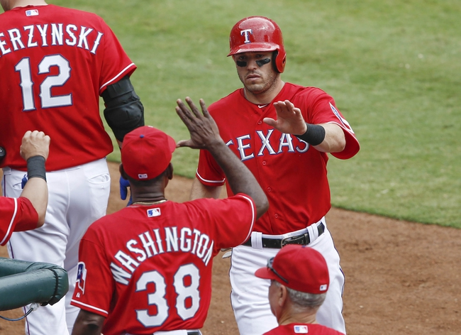 Sep 28, 2013; Arlington, TX, USA; Texas Rangers second baseman Ian Kinsler (5) is congratulated by manager Ron Washington (38) after scoring a run against the Los Angeles Angels during the first inning of a baseball game at Rangers Ballpark in Arlington. Mandatory Credit: Jim Cowsert-USA TODAY Sports