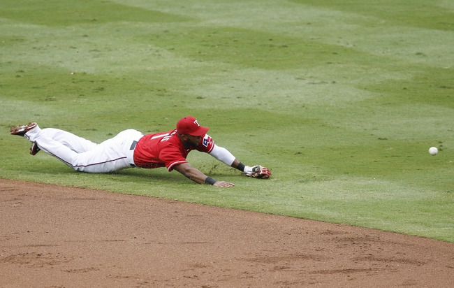 Sep 28, 2013; Arlington, TX, USA; Texas Rangers shortstop Elvis Andrus (1) dives and cannot come up with the ball hit by Los Angeles Angels first baseman Mark Trumbo (not pictured) during the second inning of a baseball game at Rangers Ballpark in Arlington. Mandatory Credit: Jim Cowsert-USA TODAY Sports