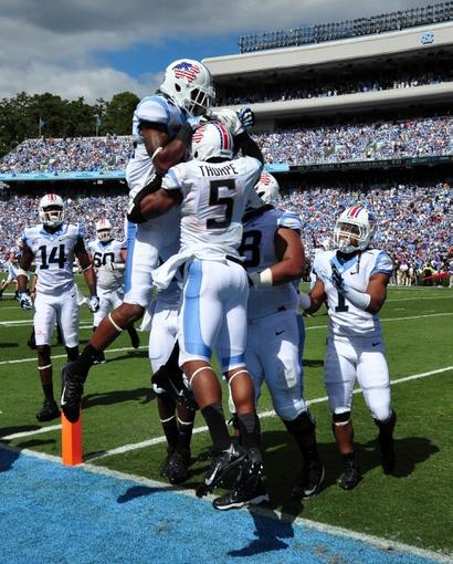 Sep 28, 2013; Chapel Hill, NC, USA; North Carolina Tarheels receiver T.J. Thorpe (5) is congratulated by teammates after a first half touchdown against the East Carolina Pirates at Kenan Memorial Stadium. Mandatory Credit: Rob Kinnan-USA TODAY Sports