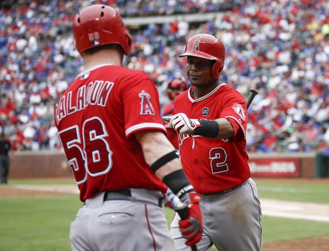 Sep 28, 2013; Arlington, TX, USA; Los Angeles Angels shortstop Erick Aybar (2) is congratulated by right fielder Kole Calhoun (56) after scoring a run against the Texas Rangers during the fifth inning of a baseball game at Rangers Ballpark in Arlington. Mandatory Credit: Jim Cowsert-USA TODAY Sports