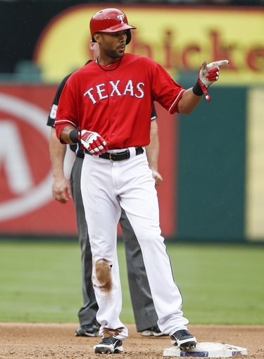 Sep 28, 2013; Arlington, TX, USA; Texas Rangers right fielder Alex Rios (51) points to the Rangers bench after hitting a double against the Los Angeles Angels during the fifth inning of a baseball game at Rangers Ballpark in Arlington. Mandatory Credit: Jim Cowsert-USA TODAY Sports