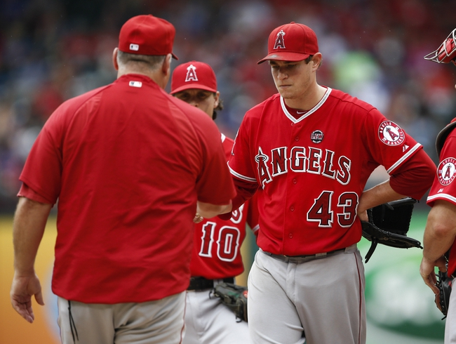 Sep 28, 2013; Arlington, TX, USA; Los Angeles Angels starting pitcher Garrett Richards (43) departs the game handing the ball over to manager Mike Scioscia (left) during the fifth inning of a baseball game against the Texas Rangers at Rangers Ballpark in Arlington. Mandatory Credit: Jim Cowsert-USA TODAY Sports