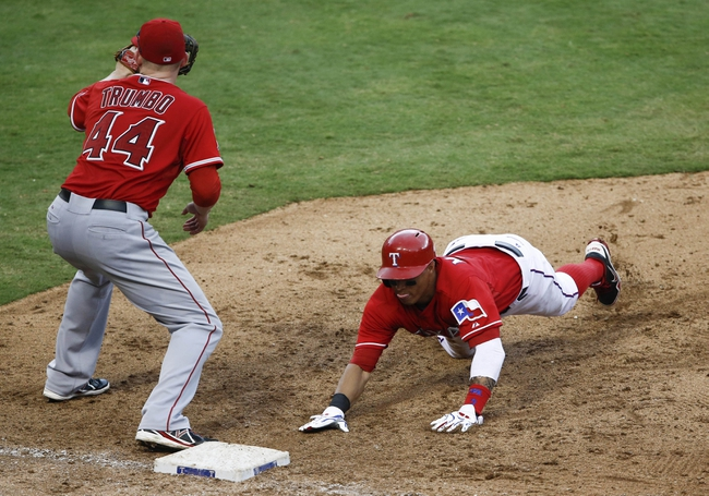 Sep 28, 2013; Arlington, TX, USA; Texas Rangers center fielder Leonys Martin (2) dives back to first ahead of the throw to Los Angeles Angels first baseman Mark Trumbo (44) during the eighth inning of a baseball game at Rangers Ballpark in Arlington. The Rangers won 7-4. Mandatory Credit: Jim Cowsert-USA TODAY Sports