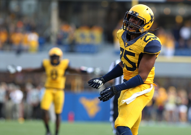Sep 28, 2013; Morgantown, WV, USA; West Virginia Mountaineers safety Darwin Cook (25) celebrates after making an interception late in the fourth quarter against the Oklahoma State Cowboys at Milan Puskar Stadium. Mandatory Credit: Peter Casey-USA TODAY Sports