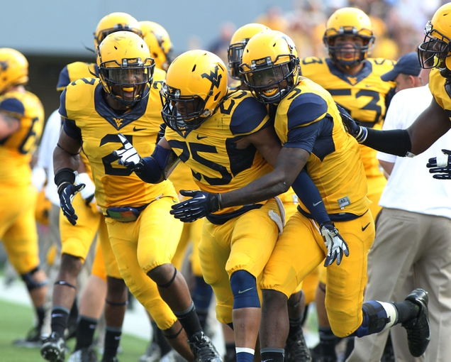Sep 28, 2013; Morgantown, WV, USA; West Virginia Mountaineers safety Darwin Cook (25) celebrates with teammates after making an interception late in the fourth quarter against the Oklahoma State Cowboys at Milan Puskar Stadium. Mandatory Credit: Peter Casey-USA TODAY Sports
