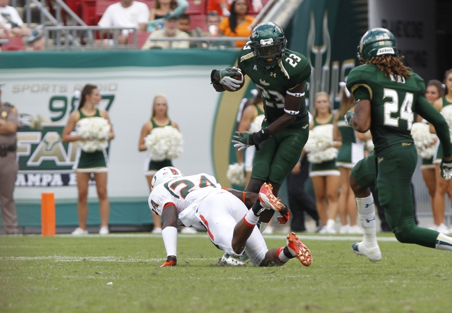 Sep 28, 2013; Tampa, FL, USA; South Florida Bulls defensive back Kenneth Durden (23) runs past Miami Hurricanes defensive back Larry Hope (24) during the second half at Raymond James Stadium. Miami Hurricanes defeated the South Florida Bulls 49-21. Mandatory Credit: Kim Klement-USA TODAY Sports