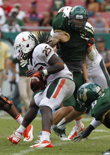 Sep 28, 2013; Tampa, FL, USA; Miami Hurricanes running back Dallas Crawford (25) runs with the ball as South Florida Bulls defensive lineman Aaron Lynch (19) defends during the second half at Raymond James Stadium. Miami Hurricanes defeated the South Florida Bulls 49-21. Mandatory Credit: Kim Klement-USA TODAY Sports
