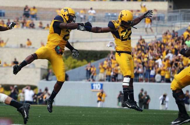 Sep 28, 2013; Morgantown, WV, USA; West Virginia Mountaineers linebacker Brandon Golson (2) and West Virginia Mountaineers cornerback Avery Williams (22) celebrate after a defensive stop against the Oklahoma State Cowboys at Milan Puskar Stadium. Mandatory Credit: Peter Casey-USA TODAY Sports