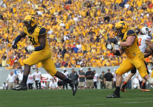 Sep 28, 2013; Morgantown, WV, USA; West Virginia Mountaineers linebacker Isaiah Bruce (31) and linebacker Jared Barber (33) celebrate after a defensive stop during the second half against the Oklahoma State Cowboys at Milan Puskar Stadium. Mandatory Credit: Peter Casey-USA TODAY Sports