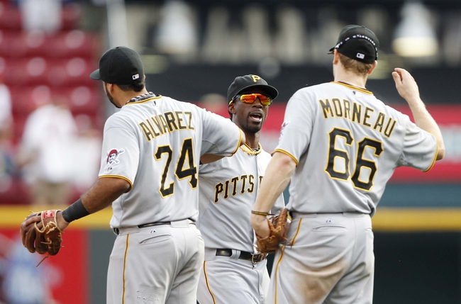 Sep 28, 2013; Cincinnati, OH, USA; Pittsburgh Pirates center fielder Andrew McCutchen (center) celebrates with third baseman Pedro Alvarez (24) and first baseman Justin Morneau (66) at the end of the game against the Cincinnati Reds at Great American Ball Park. The Pirates defeated the Reds 8-3. Mandatory Credit: Frank Victores-USA TODAY Sports