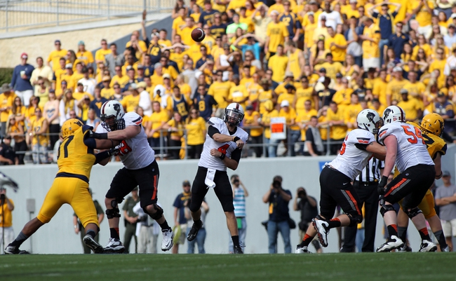 Sep 28, 2013; Morgantown, WV, USA; Oklahoma State Cowboys quarterback J.W. Walsh (4) passes the ball against the West Virginia Mountaineers at Milan Puskar Stadium. Mandatory Credit: Peter Casey-USA TODAY Sports