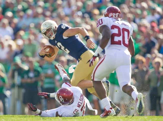 Sep 28, 2013; South Bend, IN, USA; Notre Dame Fighting Irish quarterback Andrew Hendrix (12) is pressured by Oklahoma Sooners linebacker Corey Nelson (7) and linebacker Frank Shannon (20) in the second quarter at Notre Dame Stadium. Mandatory Credit: Matt Cashore-USA TODAY Sports