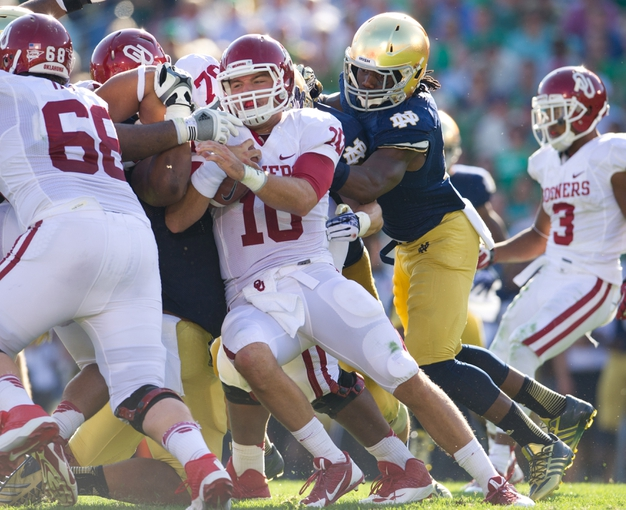 Sep 28, 2013; South Bend, IN, USA; Oklahoma Sooners quarterback Blake Bell (10) carries the ball as Notre Dame Fighting Irish linebacker Jaylon Smith (9) defends in the second quarter at Notre Dame Stadium. Mandatory Credit: Matt Cashore-USA TODAY Sports