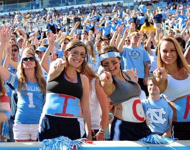 Sep 28, 2013; Chapel Hill, NC, USA; North Carolina Tarheels fans Alyssa Radel , Rachel Gogal and Mckenzie Bennet (left to right) cheer at the beginning of the fourth quarter against the East Carolina Pirates at Kenan Memorial Stadium.  ECU won 55-31. Mandatory Credit: Rob Kinnan-USA TODAY Sports