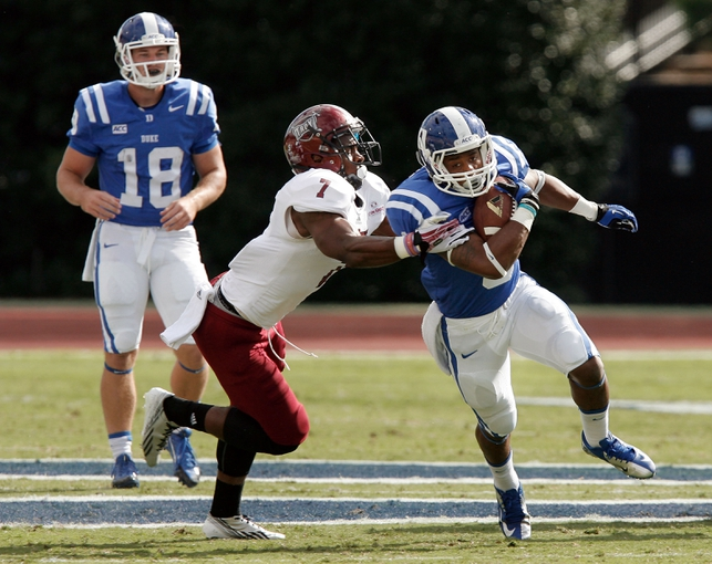 Sep 28, 2013; Durham, NC, USA;  Troy Trojans safety Chris Pickett (7) defends as Duke Blue Devils running back Josh Snead (9) runs the ball at Wallace Wade Stadium. Mandatory Credit: Mark Dolejs-USA TODAY Sports