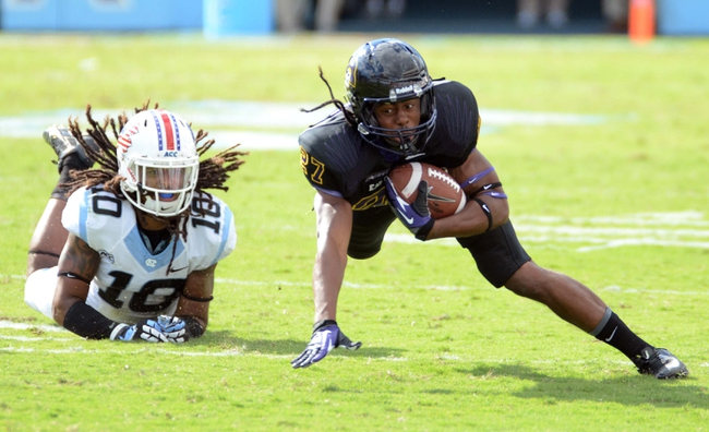 Sep 28, 2013; Chapel Hill, NC, USA; East Carolina Pirates receiver Jimmy Williams (27)  dives forward for yards after being tripped up by North Carolina Tarheels safety Tre Boston (10) during the second half at Kenan Memorial Stadium.  ECU won 55-31. Mandatory Credit: Rob Kinnan-USA TODAY Sports