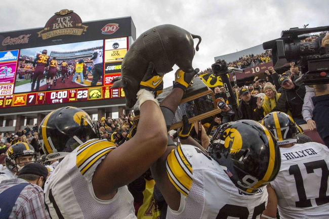 Sep 28, 2013; Minneapolis, MN, USA; Iowa Hawkeyes team hold up the Floyd of Rosedale trophy after beating the Minnesota Golden Gophers at TCF Bank Stadium. The Hawkeyes won 23-7. Mandatory Credit: Jesse Johnson-USA TODAY Sports