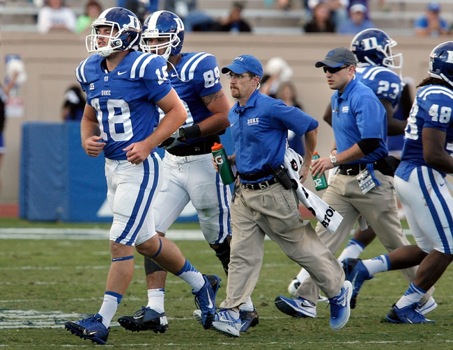 Sep 28, 2013; Durham, NC, USA;  Duke Blue Devils quarterback Brandon Connette (18) is escorted off the field by trainers after a brief injury against the Troy Trojans at Wallace Wade Stadium. Mandatory Credit: Mark Dolejs-USA TODAY Sports