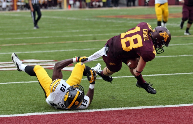 Sep 28, 2013; Minneapolis, MN, USA; Minnesota Golden Gophers wide receiver Derrick Engel (18) dives to the end zone for a touchdown as Iowa Hawkeyes quarterback Cody Sokol (19) attempts to make a tackle in the second half at TCF Bank Stadium. The Hawkeyes won 23-7. Mandatory Credit: Jesse Johnson-USA TODAY Sports