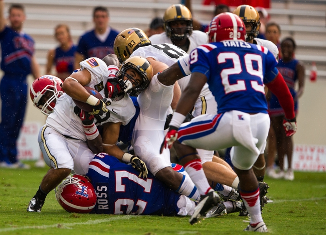 Sep 28, 2013; Dallas, TX, USA; Army Black Knights fullback Tirone Young (38) is tackled by the Louisiana Tech Bulldogs during second quarter at the Cotton Bowl Stadium. Mandatory Credit: Jerome Miron-USA TODAY Sports