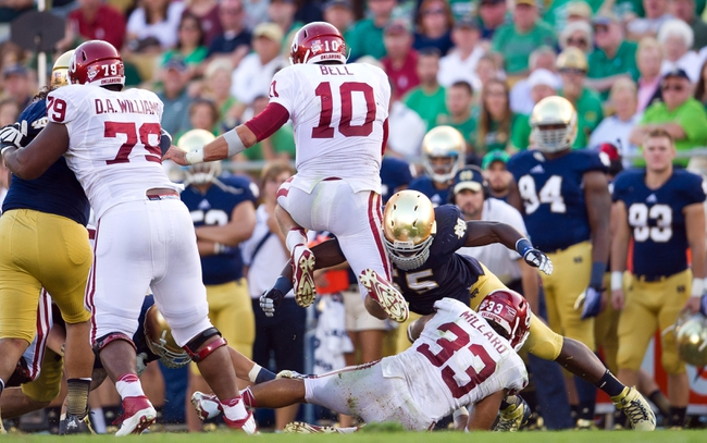 Sep 28, 2013; South Bend, IN, USA; Oklahoma Sooners quarterback Blake Bell (10) carries the ball as Notre Dame Fighting Irish linebacker Prince Shembo (55) attempts to tackle in the fourth quarter at Notre Dame Stadium. Oklahoma won 35-21. Mandatory Credit: Matt Cashore-USA TODAY Sports