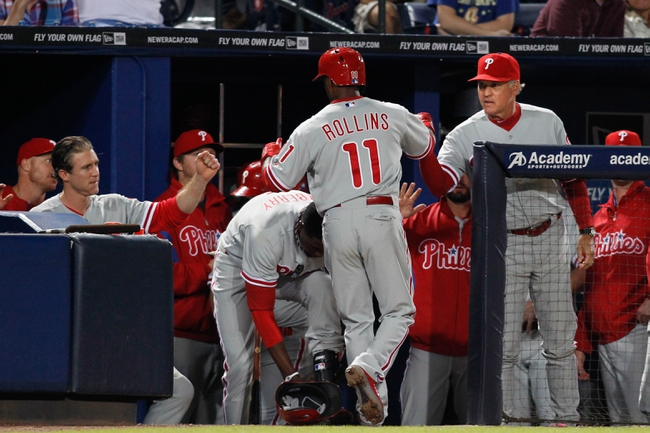 Sep 28, 2013; Atlanta, GA, USA; Philadelphia Phillies shortstop Jimmy Rollins (11) is congratulated by manager Ryne Sandberg (23) after scoring a run against the Atlanta Braves in the seventh inning at Turner Field. Mandatory Credit: Brett Davis-USA TODAY Sports