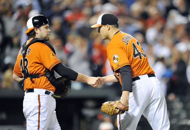 Sep 28, 2013; Baltimore, MD, USA; Baltimore Orioles catcher Chris Snyder (48) congratulates closer Jim Johnson after a game against the Boston Red Sox at Oriole Park at Camden Yards. The Orioles defeated the Red Sox 6-5. Mandatory Credit: Joy R. Absalon-USA TODAY Sports
