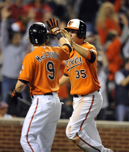 Sep 28, 2013; Baltimore, MD, USA; Baltimore Orioles teammates Nate McLouth (9) and Danny Valencia (35) high-five each other after scoring the game winning runs in the eight inning on a two-run rbi double by Steve Pearce (not shown) against the Boston Red Sox at Oriole Park at Camden Yards. The Orioles defeated the Red Sox 6-5. Mandatory Credit: Joy R. Absalon-USA TODAY Sports