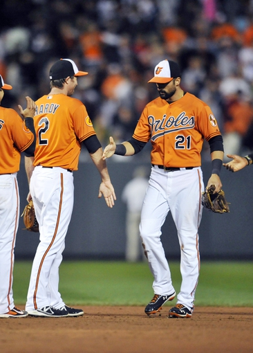 Sep 28, 2013; Baltimore, MD, USA; Baltimore Orioles teammates J.J. Hardy (2) and Nick Markais (21) celebrate after a game against the Boston Red Sox at Oriole Park at Camden Yards. The Orioles defeated the Red Sox 6-5. Mandatory Credit: Joy R. Absalon-USA TODAY Sports