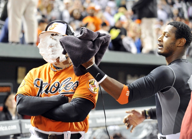 Sep 28, 2013; Baltimore, MD, USA; Baltimore Orioles designated hitter Steve Pearce (28) gets a shaving cream pie from Adam Jones (right) after a game against the Boston Red Sox at Oriole Park at Camden Yards. The Orioles defeated the Red Sox 6-5. Mandatory Credit: Joy R. Absalon-USA TODAY Sports