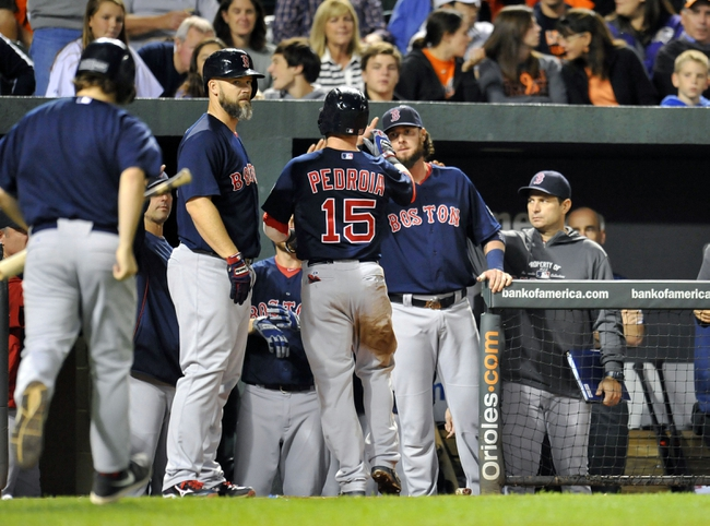 Sep 28, 2013; Baltimore, MD, USA; Boston Red Sox second baseman Dustin Pedroia (15) is congratulated by teammates after scoring in the seventh inning against the Baltimore Orioles at Oriole Park at Camden Yards. The Orioles defeated the Red Sox 6-5. Mandatory Credit: Joy R. Absalon-USA TODAY Sports