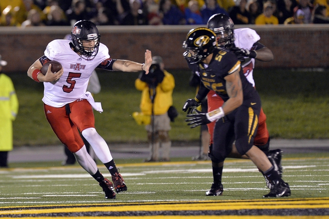 Sep 28, 2013; Columbia, MO, USA; Arkansas State Red Wolves quarterback Adam Kennedy (5) reaches out to block a tackle from Missouri Tigers defensive back Jared Edwards (46) during the second half at Faurot Field. Mandatory Credit: Jasen Vinlove-USA TODAY Sports