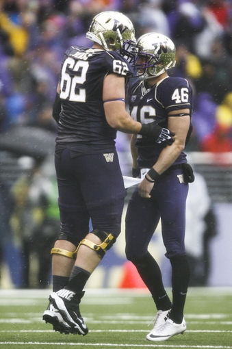 Sep 28, 2013; Seattle, WA, USA; Washington Huskies kicker Travis Coons (46) celebrates with Washington Huskies offensive linesman Ross Dolbec (62) after kicking a 42-yard field goal against the Arizona Wildcats during the second quarter at Husky Stadium. Mandatory Credit: Joe Nicholson-USA TODAY Sports