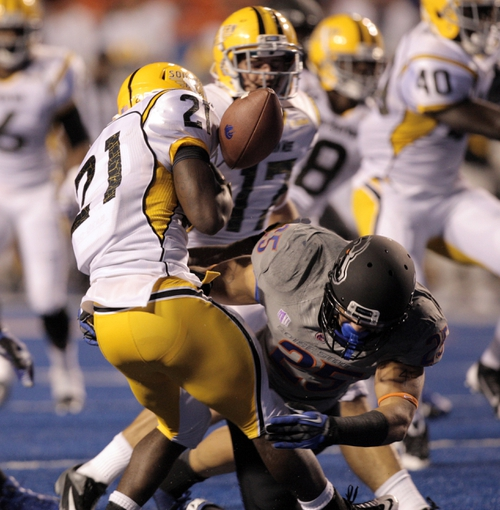 Sep 28, 2013; Boise, ID, USA; Southern Miss Golden Eagles running back Jeremy Hester (21) has the ball knocked loose by Boise State Broncos linebacker Christopher Santini (25) on a kick off return during the first half against the Boise State Broncos at Bronco Stadium. Mandatory Credit: Brian Losness-USA TODAY Sports