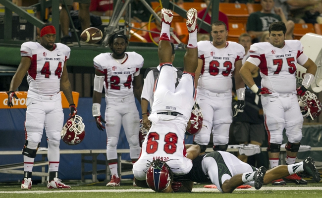 Sep 28, 2013; Honolulu, HI, USA; Fresno State tight end Marcel Jensen (89) flips over Hawaii linebacker Kamalani Alo (47) and fumbles the ball out of bounds during the first quarter of the NCAA college football game at Aloha Stadium. Mandatory Credit: Marco Garcia-USA TODAY Sports