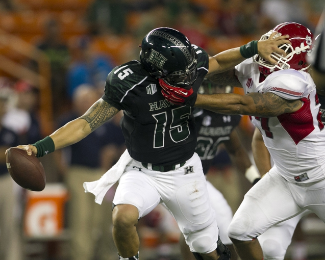 Sep 28, 2013; Honolulu, HI, USA; Hawaii quarterback Ikaika Woolsey (15) is sacked by Fresno State linebacker Donavon Lewis (27) during the first quarter of the NCAA college football game at Aloha Stadium. Mandatory Credit: Marco Garcia-USA TODAY Sports